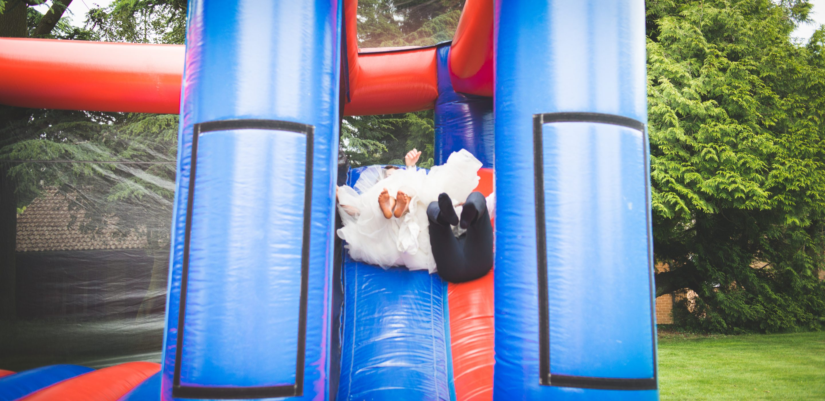 bouncy castle, bride and groom, highgate house hotel, wedding photographer wedding photography northamptonshire