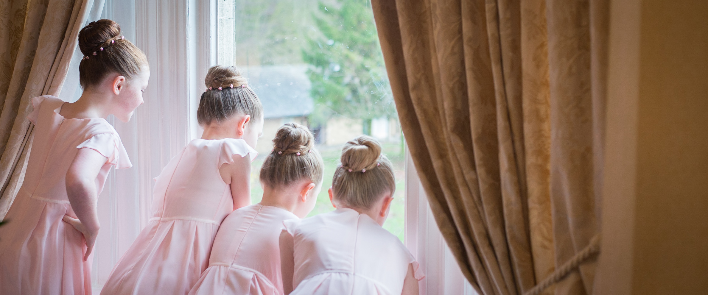 Bridesmaids looking out of the window during bridal prep. Wedding photography. www.gemmawillisphotography.co.uk