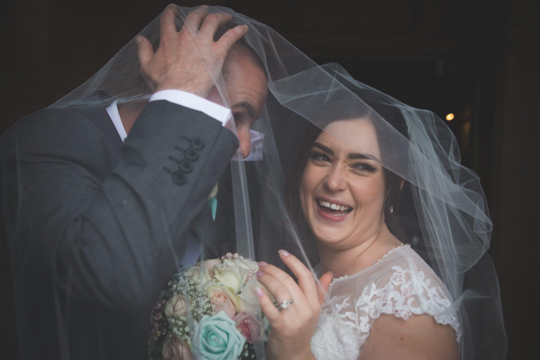 Jocelyn and Dan under the veil having a cheeky little kiss.